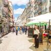 Un serveur se tient devant des terrasses de restaurants dans une rue de Lisbonne.