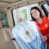Une employée du service Tide Dry Cleaners tient des vêtements dans l'embrasure d'une portière de voiture.