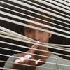 Andrew Garfield regarde à travers les stores d'une fenêtre dans cette image tirée du film <i>Under the Silver Lake</i>, de David Robert Michell.