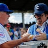 Un homme donne un hot-dog à un autre homme.