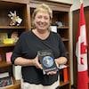 Une femme dans son bureau parlementaire tien son livre