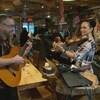 Un homme joue de la guitare et une femme joue du violon dans un restaurant, devant les clients.