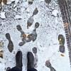 Point de vue en autoportrait d'une paire de bottes noires dans la neige.