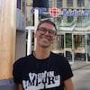 Un homme est appuyé contre une colonne à l'avant de l'édifice de Radio-Canada.