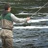 Un pêcheur est debout dans l'eau.