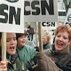 Des femmes tiennent des pancartes de la CSN et criant des slogans.
