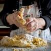 Gros plan sur les mains pleines de pâte d'une vieille dame qui prépare des pâtes fraîches.