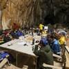 Une quinzaine de personnes réunit autour d'une table dans une immense grotte.