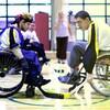 Deux adolescents en fauteuil roulant jouent au hockey.