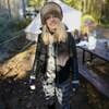 Photo d'Evelyne Charuest, habillée en vêtements d'extérieur, avec des bottes et un chapeau de fourrure, qui pose devant une tente de camping.