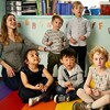 Photo d'une éducatrice assise dans une salle de garderie avec six jeunes enfants.