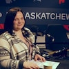 Kymber Zahar est assise dans le studio de radio de Radio-Canada Saskatchewan