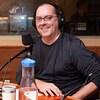 L'homme chauve à lunettes sourit franchement en studio.
