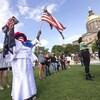 Des manifestants, dont une femme brandissant dans chaque main le drapeau des États-Unis, sont devant un édifice parlementaire.