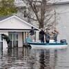 Des gens sur un canot examinent une maison inondée