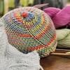 Un sein tricoté, deux épingles à tricoter du fil de coton sur une table.