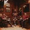 Photo de quatre hommes portant des chemises ou une veste à carreaux dans un chalet en bois traditionnel.