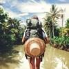 Une personne portant un sac à dos se tient devant une rivière.