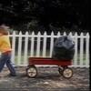 Un enfant tire un chariot qui contient un sac à déchets en plastique.
