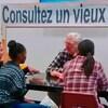 Un homme âgé assis à un kiosque devant trois étudiantes.
