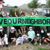 Des personnes tiennent une bannière avec les mots: sauvez notre quartier.