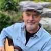 Le musicien Robert Walsh avec sa guitare dans un jardin