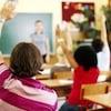 Des élèves lèvent la main dans une salle de classe.