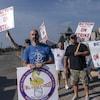 Des travailleurs brandissent des pancartes.