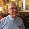 Un curé sourit à la caméra avec l'intérieur de l'église en arrière-plan.