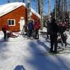 Chalet du club de ski  de fond Les sentiers de la rivière Amédée à Baie-Comeau : on aperçoit des fondeurs dehors, en plein hiver