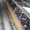 Des dizaines de personnes attendent l'arrivée du train léger à la station Tunney's Pasture.