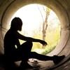 Une jeune fille est assise dans un tuyau d'égout et regarde vers la sortie.