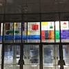 Un vitrail avec les éléments du tableau périodique de différente couleurs.