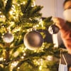 Une femme portant un masque décore un sapin de Noël.