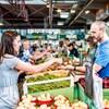 Une femme donne de la monnaie à un commerçant pour acheter des légumes.