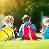 Une fille et deux garçons sont assis dans un parc avec leurs sac à dos.