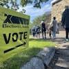 En avant-plan, une affiche indiquant la direction d'un bureau de vote et, en arrière-plan, une file d'attente.