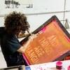 Yasmine Louis, sérigraphiste travaille sur un écran de soie tendu sur un cadre en bois