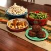 Un bol de maïs soufflé, un plat de poutine penjadbi, un bol d'edamame et une assiette de croquettes de crabe.