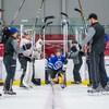 Un enfant patine sous une haie d'honneur formée de bâtons de hockey.