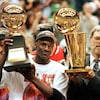 Michael Jordan et l'entraîneur Phil Jackson hissant des trophées après avoir remporté leur sixième championnat en juin 1998.
