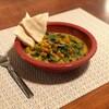 Un bol de ragoût de pois chiches accompagné de pain pita et d'une fourchette.