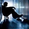 Un jeune homme assis entre des casiers dans une école semble perdu dans ses pensées.