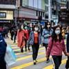 Des piétons portant des masques traversent une rue.
