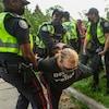 Trois officiers de police tiennent les membres d'un homme pour l'appréhender.