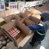 Une bénévole prépare des cartons de nourriture.