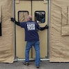 Un homme termine d'installer une tente médicale beige