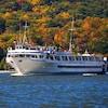 Le navire Grande Caribe vogue devant des arbres feuillus aux teintes automnales.