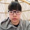 Une jeune femme: cheveux bruns, lunettes, toupet