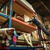 Une femme sur une échelle qui tient un meuble en bois sur une étagère dans un grand entrepôt.